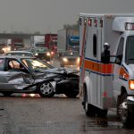 Totaled car on highway with ambulance nearby.