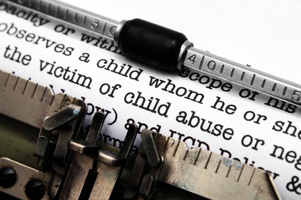 Close up text on paper in a type writer focused on the words victim of child abuse